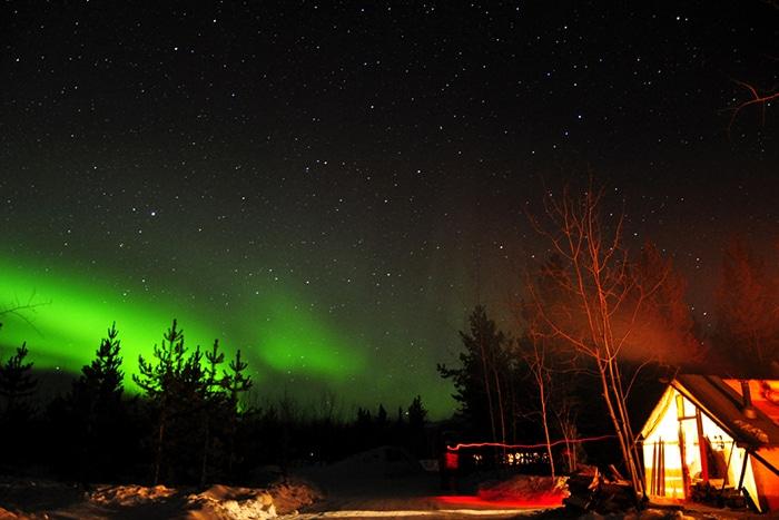 Cabana e a Aurora Boreal ao fundo   Foto por Livia Auler