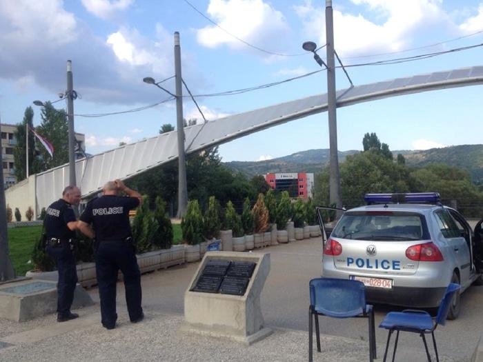 Ponte de Mitrovice com policiais poloneses, com a bandeira sérvia ao fundo | Foto por Sabrina Sasaki