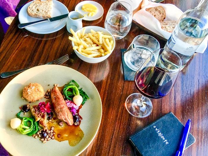 Mesa farta no Aqua Shard, prato principal, acompanhamentos um bom vinho e o caderno de anotações do Viajante.